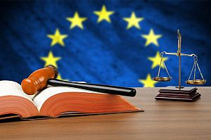 Still life photo of a gavel, scales of justice and law book on a judges bench with the European Union flag behind.